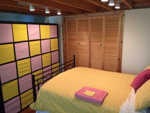 Sleep in style behind our colorful wall that doubles as an immense amount of storage.  This room also has access to a full bathroom and a private patio....oh la la!